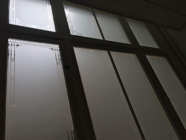Raamdecoratie van raamfolie met het effect van gezandstraald glas aangebracht bij advocatenkantoor Rutgers & Posch in Amsterdam.